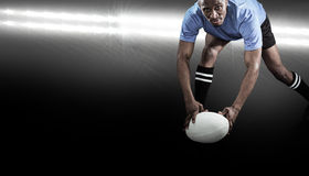 Composite image of portrait of sportsman bending and holding ball while playing rugby. Portrait of sportsman bending and holding ball while playing rugby against royalty free stock images