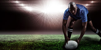 Composite image of portrait of sportsman bending and holding ball while playing rugby Royalty Free Stock Image