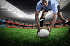 Composite image of portrait of sportsman bending and holding ball while playing rugby. Portrait of sportsman bending and holding ball while playing rugby against stock photos