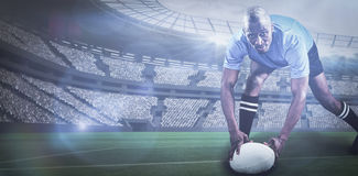 Composite image of portrait of sportsman bending and holding ball while playing rugby with. Portrait of sportsman bending and holding ball while playing rugby royalty free stock photo
