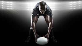 Composite image of portrait of sportsman holding ball while playing rugby. Portrait of sportsman holding ball while playing rugby against spotlight stock images