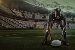 Composite image of portrait of sportsman holding ball while playing rugby with 3d. Portrait of sportsman holding ball while playing rugby against rugby stadium stock photos