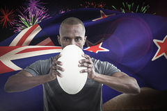 Composite image of portrait of sportsman pressing rugby ball Royalty Free Stock Image