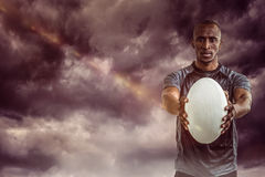 Composite image of portrait of sportsman showing rugby ball Royalty Free Stock Images