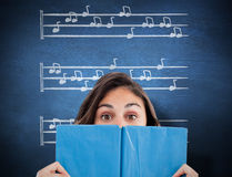 Composite image of portrait of a student hiding behind a blue book Stock Image