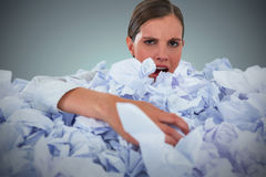 Composite image of portrait of unhappy businesswoman in heap crumpled paper Royalty Free Stock Photo