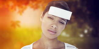 Composite image of portrait of upset woman with blank note on forehead Royalty Free Stock Image