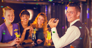 Composite image of portrait of waiter and beautiful women standing at bar counter Stock Image