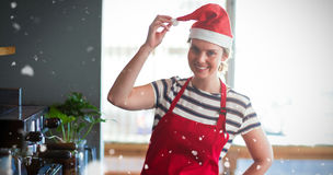 Composite image of portrait of waitress in santa hat standing with hand on hip Stock Photo
