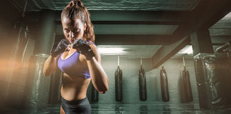 Composite image of portrait of woman with fighting stance. Portrait of woman with fighting stance against red boxing area with punching bags stock image