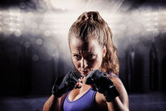 Composite image of portrait of woman with fighting stance Royalty Free Stock Photos
