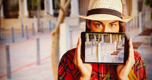 Composite image of portrait of woman hiding face with digital tablet Stock Images