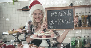 Composite image of portrait of woman holding blackboard with merry christmas Stock Images