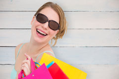 Composite image of portrait of a woman holding shopping bags wearing sunglasses Stock Images