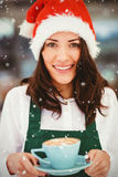 Composite image of portrait of woman with santa hat holding coffee Stock Photos
