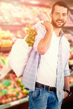 Composite image of portrait of young man carrying vegetables in shopping bag Stock Image