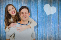 Composite image of portrait of young man giving piggy back to girlfriend Stock Images