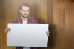 Composite image of portrait of young man holding blank placard. Portrait of young man holding blank placard against wooden surface with planks Stock Image