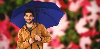 Composite image of portrait of young man holding blue umbrella. Portrait of young man holding blue umbrella against maple leaves fallen on grass Stock Photo