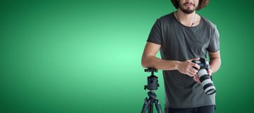 Composite image of portrait of young photographer holding digital camera. Portrait of young photographer holding digital camera against green vignette Stock Image