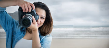 Composite image of portrait of young woman photographing through camera Stock Image