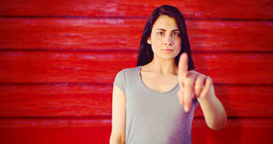 Composite image of portrait of young woman pointing. Portrait of young woman pointing against full frame shot of red wall Royalty Free Stock Photo