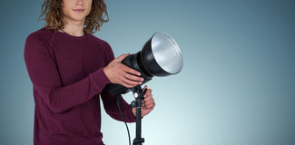 Composite image of portraot of young photographer holding focus light. Portraot of young photographer holding focus light against grey vignette stock photos
