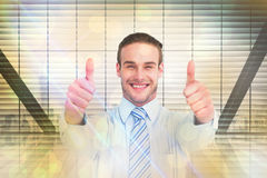 Composite image of positive businessman smiling with thumbs up Stock Photo