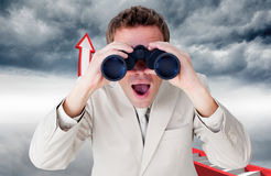 Composite image of positive businessman using binoculars Stock Photo