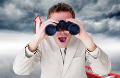 Composite image of positive businessman using binoculars Stock Photo