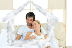 Composite image of positive couple drinking coffee lying in the bed Stock Photo