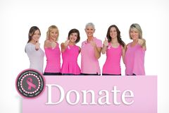 Composite image of positive women posing with pink top for breast cancer Royalty Free Stock Photos