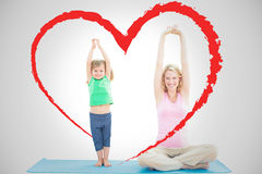 Composite image of pregnant mother and daughter doing yoga together. Pregnant mother and daughter doing yoga together against heart Royalty Free Stock Photo