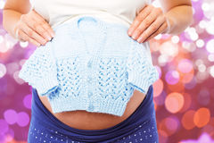 Composite image of pregnant woman holding baby clothes. Pregnant woman holding baby clothes against glowing background Royalty Free Stock Photos