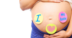 Composite image of pregnant woman with stickers on bump Royalty Free Stock Photo