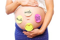 Composite image of pregnant woman with stickers on bump Royalty Free Stock Photography