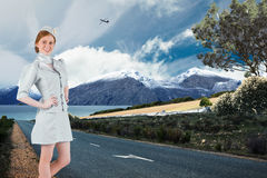 Composite image of pretty air hostess with hand on hip Royalty Free Stock Images