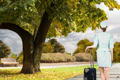 Composite image of pretty air hostess leaning on suitcase Stock Photo