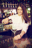 Composite image of pretty bartender pouring blue martini drink in glass Royalty Free Stock Images