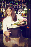 Composite image of pretty bartender pouring whiskey in glass Stock Image