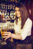 Composite image of pretty bartender serving beer Royalty Free Stock Photography