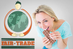 Composite image of pretty blonde eating bar of chocolate. Pretty blonde eating bar of chocolate against grey vignette royalty free stock image