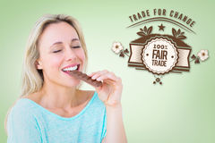 Composite image of pretty blonde enjoying and eating bar of chocolate. Pretty blonde enjoying and eating bar of chocolate against green vignette royalty free stock photos