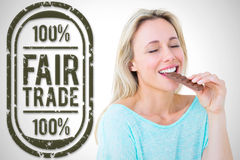 Composite image of pretty blonde enjoying and eating bar of chocolate. Pretty blonde enjoying and eating bar of chocolate against white background with vignette royalty free stock photo