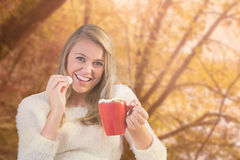 Composite image of pretty blonde enjoying hot chocolate on the couch Royalty Free Stock Photography