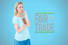 Composite image of pretty blonde feeling guilty to eat bar of chocolate Royalty Free Stock Image