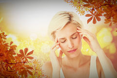 Composite image of pretty blonde with headache touching her temples Stock Images