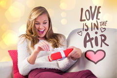 Composite image of pretty blonde opening a gift. Pretty blonde opening a gift against yellow abstract light spot design Royalty Free Stock Photo