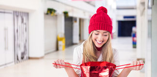 Composite image of pretty blonde opening gift bag. Pretty blonde opening gift bag against interior of modern shopping mall Stock Photo
