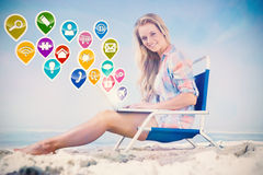 Composite image of pretty blonde sitting on beach using her laptop Stock Images